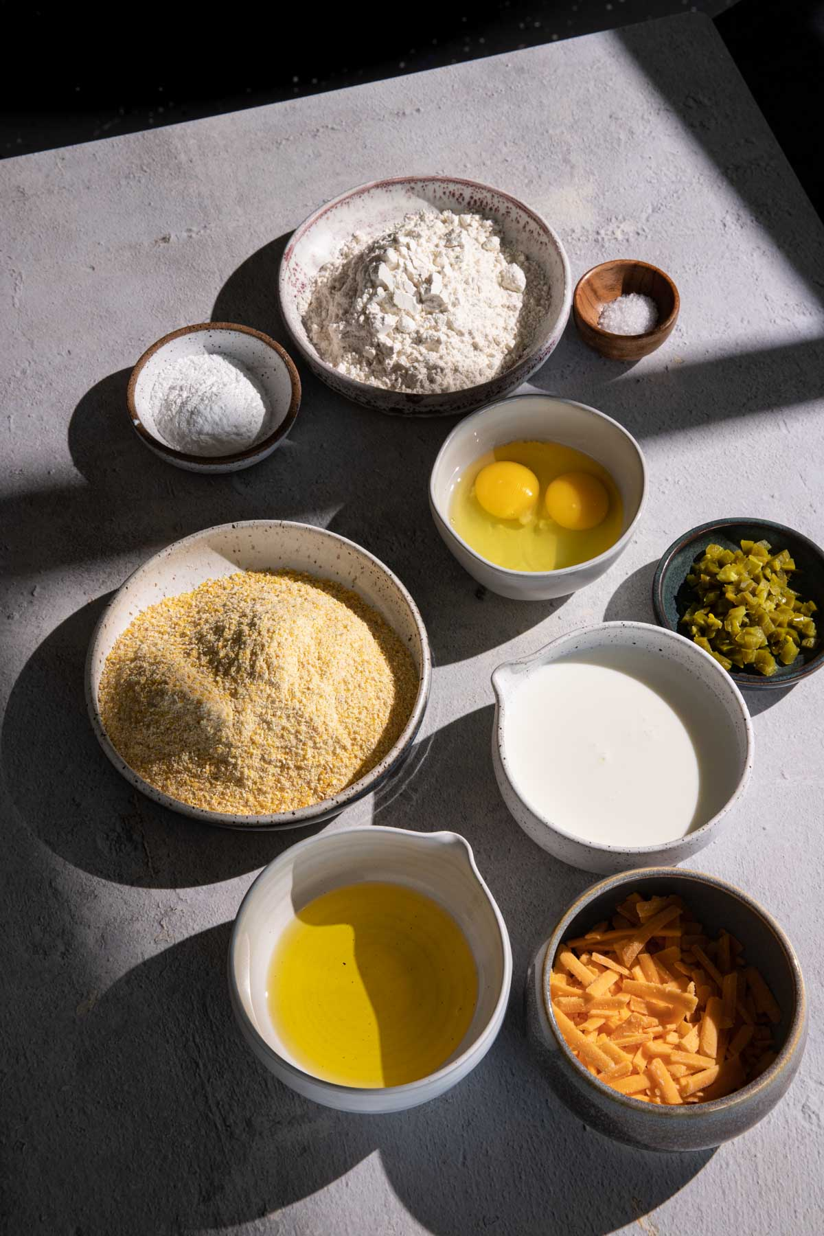 Flour, cornmeal, eggs, cheddar cheese, oil, in separate bowls