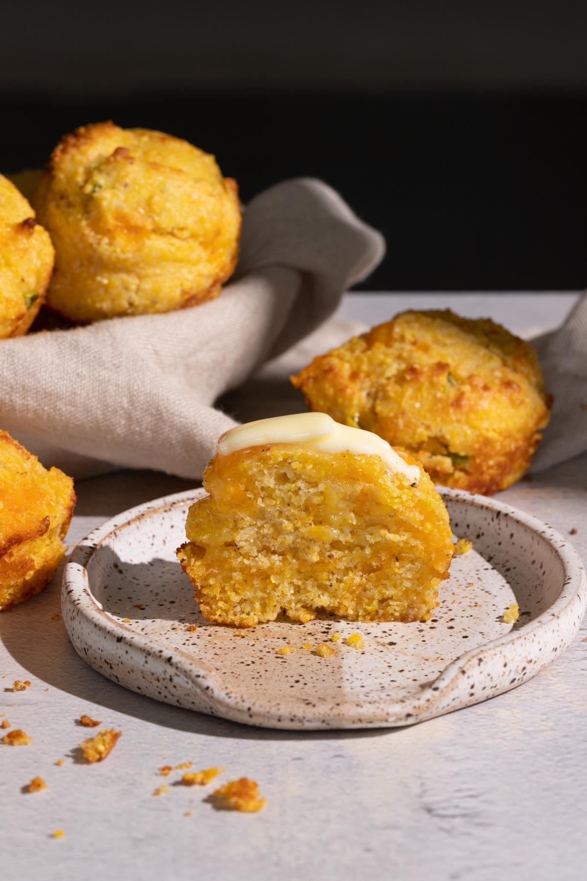 Jalapeno cheddar cornbread muffin on a plate cut in half