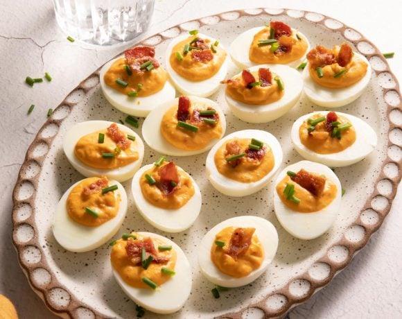 Pimento Bacon Deviled eggs on an oval clay plate