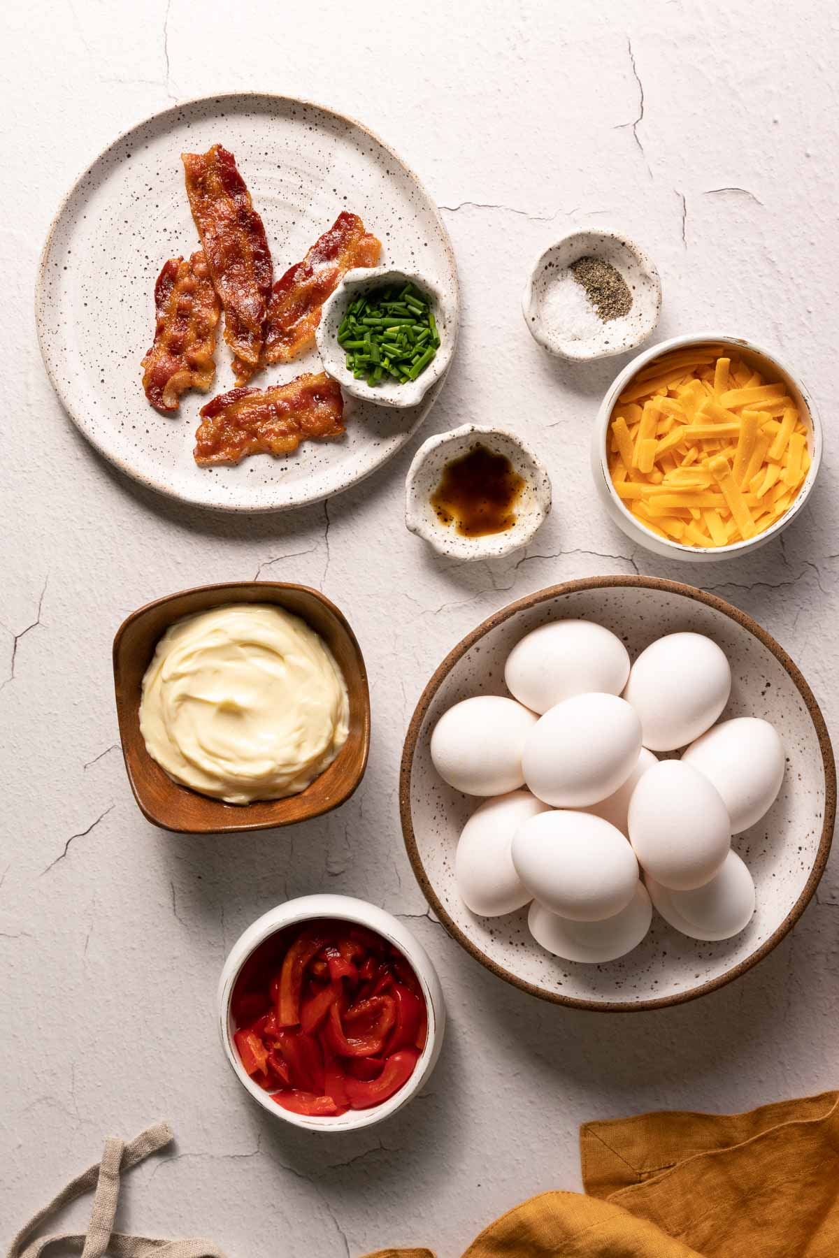 Eggs, bacon, mayo, cheese, and pimentos in bowls