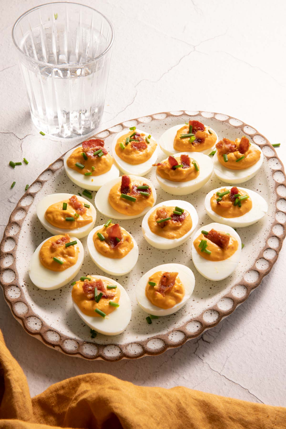Deviled eggs with bacon on an oval plate and a glass of water