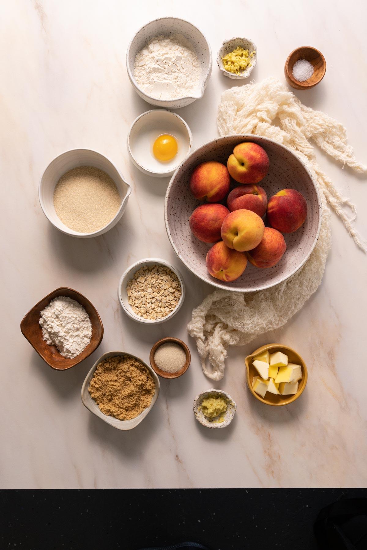 Bowls of peaches, flour, sugar, butter, and oats for a peach crostata