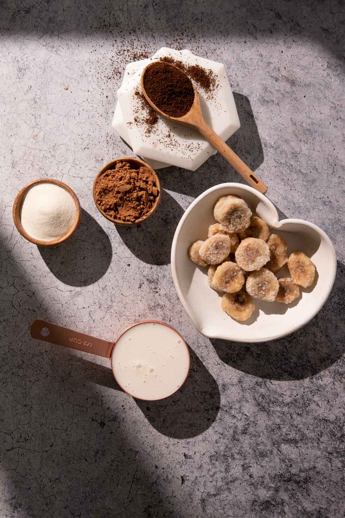 A bowl of frozen bananas, milk, collagen powder, and cocoa powder