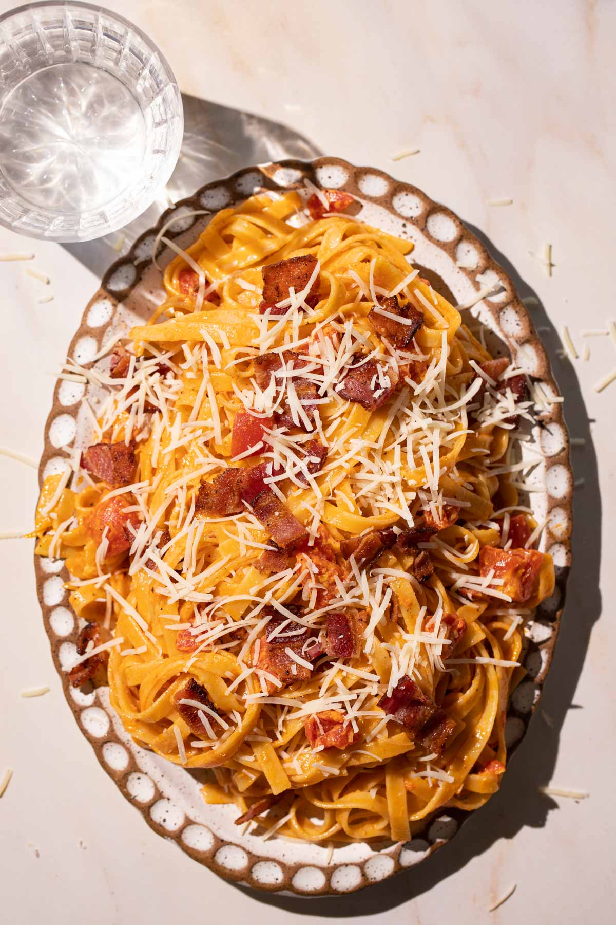 Creamy Tomato Bacon pasta with cheese on a pottery plate