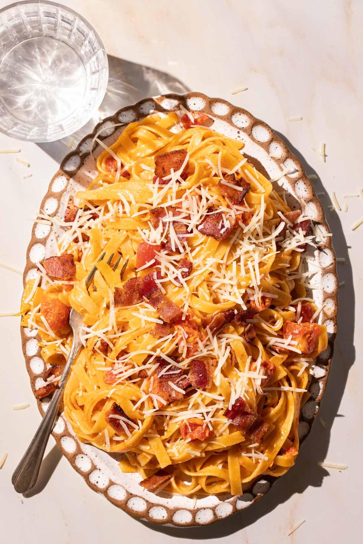 Pasta with bacon and tomatoes on an oval plate