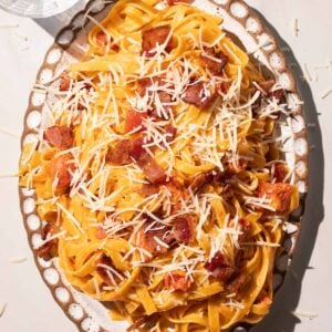 Creamy Tomato bacon pasta on a pottery plate