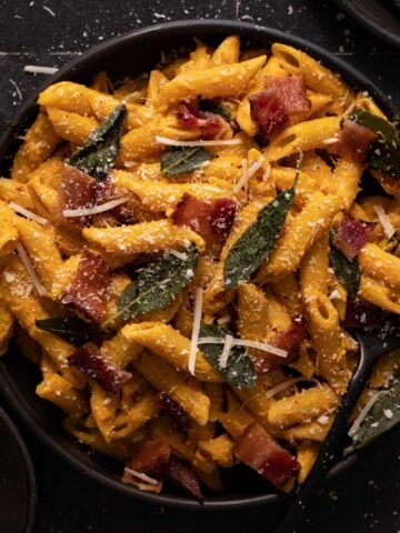 Pumpkin pasta with bacon, sage, and parmesan cheese on a black plate