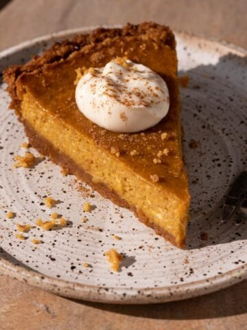 A slice of cream cheese pumpkin pie on a plate with a fork