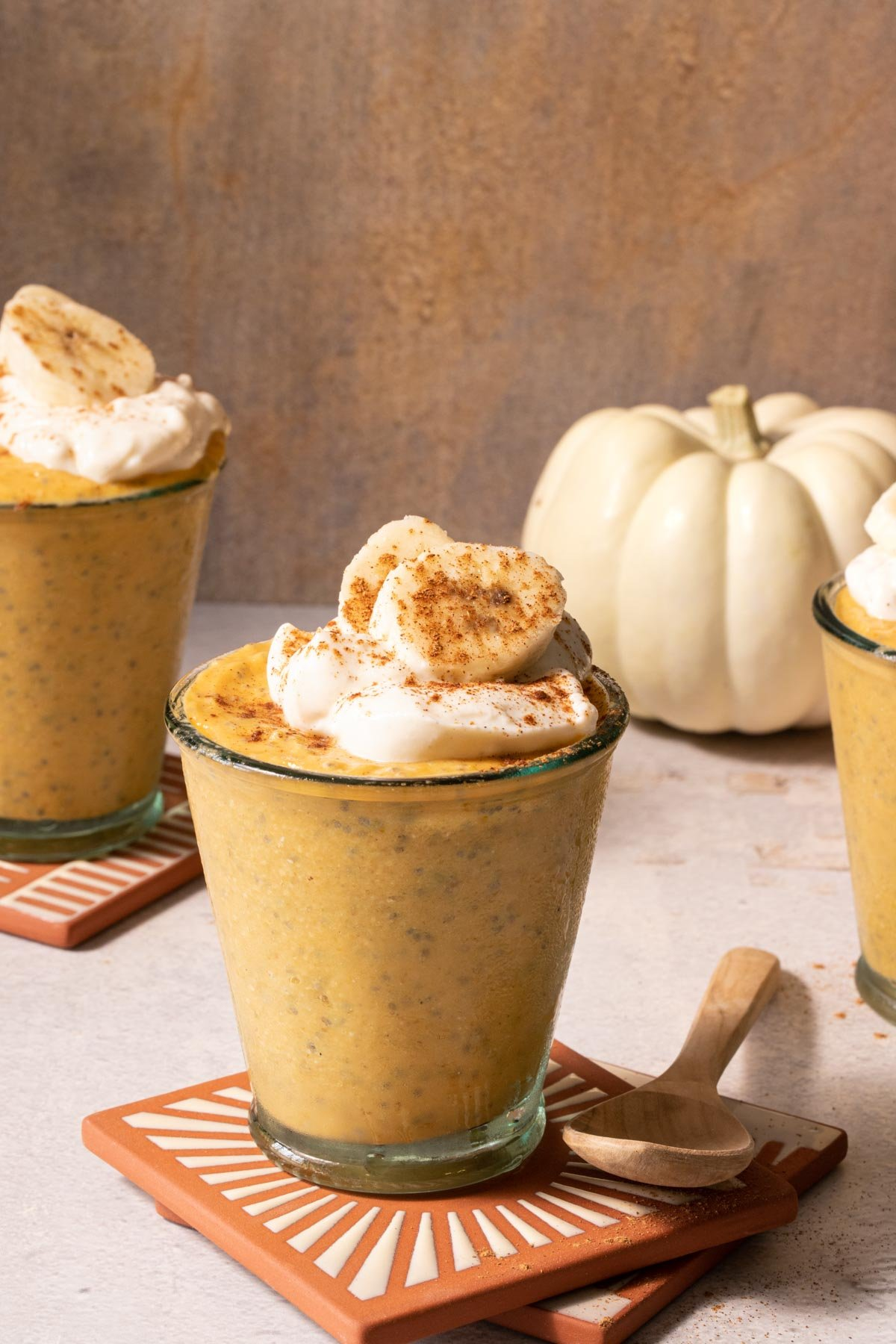 Pumpkin chia pudding in glasses with sliced banana and pumpkins